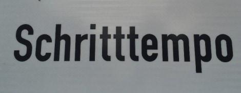 """Schild, auf dem das Wort Schritttempo korrekt mit drei gleichlautenden Konsonanten - dem """"t"""" - geschrieben ist."""