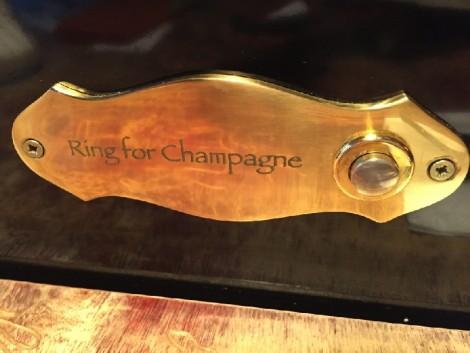 """Auf dem Bild ist ein Klingelschild zu sehen, auf dem steht """"Ring for Champagne"""""""