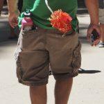 Auf dem Foto ist ein Mann zu sehen, der eine pinkfarbene Kindertrinkflasche in der Hosentasche hat