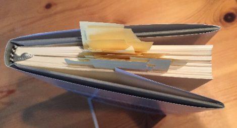 """Von oben wird auf """"Sitze im Buch"""" geblickt, es gespickt mit Merkzetteln"""