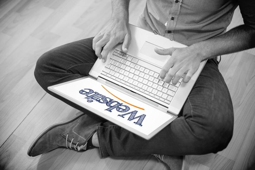 Auf dem Foto ist eine Frau mit Laptop zu sehen, auf dem das Wort Website steht.