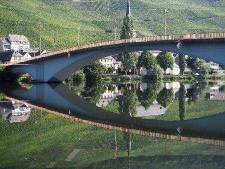 Schein oder Sein? Auf dem Foto spiegelt sich eine Brücke im Wasser.