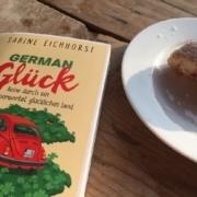 """Das Buch """"German Glück"""" liegt im Sonnenschein, ein angebissener Berliner daneben - manchmal reicht das zum Glücklichsein"""