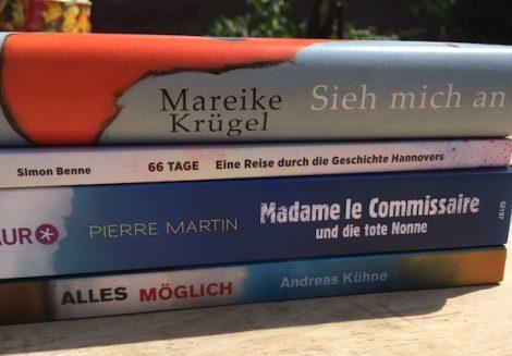 """Bücherstapel mit unter anderem dem Buch des Monats: """"66 Tage. Eine Reise durch die Geschichte Hannovers""""."""